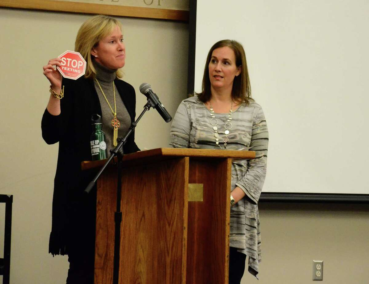 Wendy Pratt, left, and Stephanie Kushner, co-presidents of the New Canaan High School's Parent Faculty Association, show a bumper sticker that was given to attendees of a Safe Driving Month event March 12, 2014, at the school. Jacy Good, who lost her parents during a crash caused by a distracted driver in 2008, spoke to students and parents attending the event about the dangers of using a cellphone behind the wheel.