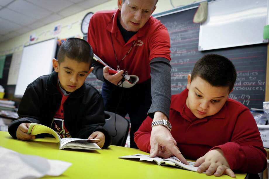 John Ureste, 7, right, practices reading with the help of second grade teacher Mark Cwenar Jan. 30, 2014 in Houston at Scarborough Elementary School. Carlos Soto, 7, is at left.  (Eric Kayne/For the Chronicle) Photo: Eric Kayne / Eric Kayne
