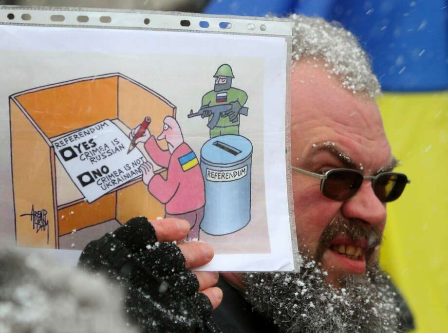 There's no wrong answer: A demonstrator in Vilnius, Lithuania, holds a cartoon poster suggesting the 