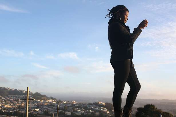 Porsha Lewis photographs the sunset at Lakeview & Ashton Mini Park at Merced Heights on March 24, 2013 in San Francisco, Calif. It was Porsha's first visit to the park, she was visiting visiting a friend who had just moved to a house down the street with her sister.