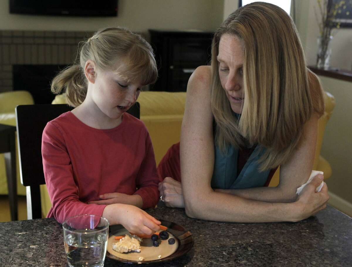 Seven-year-old Brooke Reid enjoys a mid-afternoon snack with her mother Katherine at their home in Fremont, Calif. on Wednesday, March 12, 2014. Katherine Reid completely changed Brooke's diet as a way to control her autism.