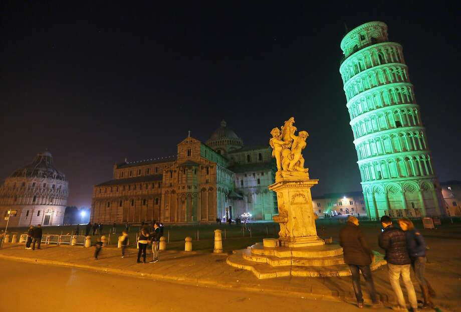 """The greening Tower of Pisa:Italy's iconic landmark turns green to celebrate   Ireland's national holiday. The St. Patrick's Day event was part of """"Global   Greening,"""" an initiative sponsored by Tourism Ireland during which famous monuments   of many world cities are bathed in green to show friendship with the Emerald   Island. Photo: Fabio Muzzi, AFP/Getty Images"""