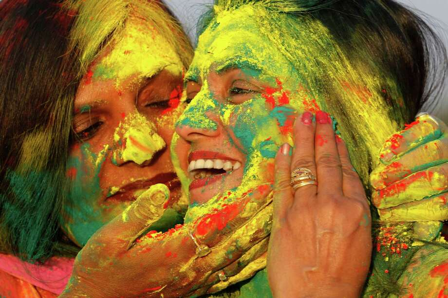 "Indian women smear colors on their faces as they celebrate ""Holi,"" a festival of colors, in Allahabad, India, Sunday, March 16, 2014. The festival heralds the arrival of spring. Photo: Rajesh Kumar Singh, AP / AP"
