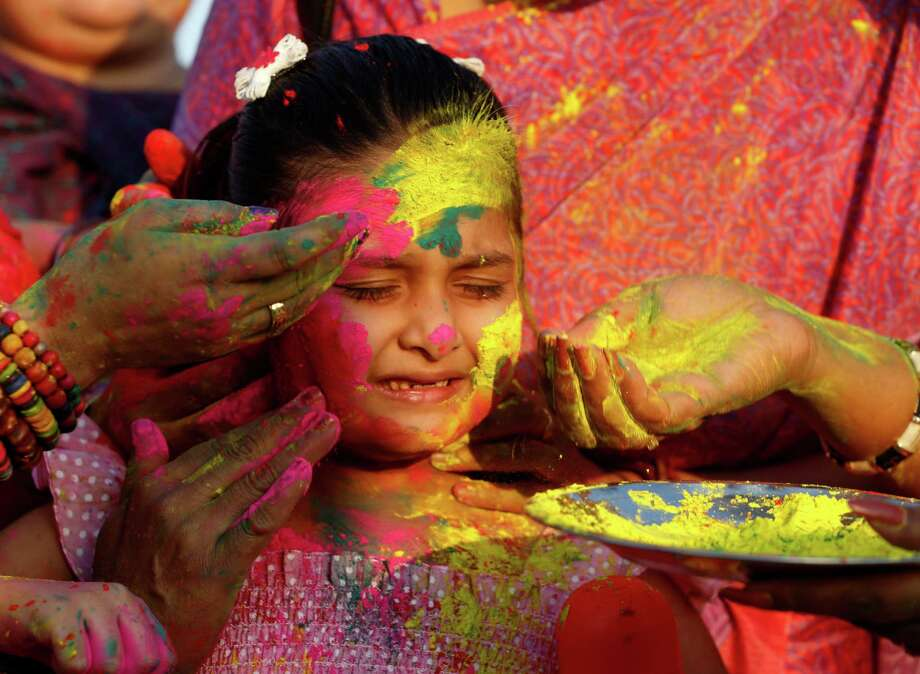 A girl reacts as women smear color on her face to  celebrate Holi, the Hindu festival of colors, in Allahabad, , India, Sunday, March 16, 2014. The festival heralds the arrival of spring. Photo: Rajesh Kumar Singh, AP / AP