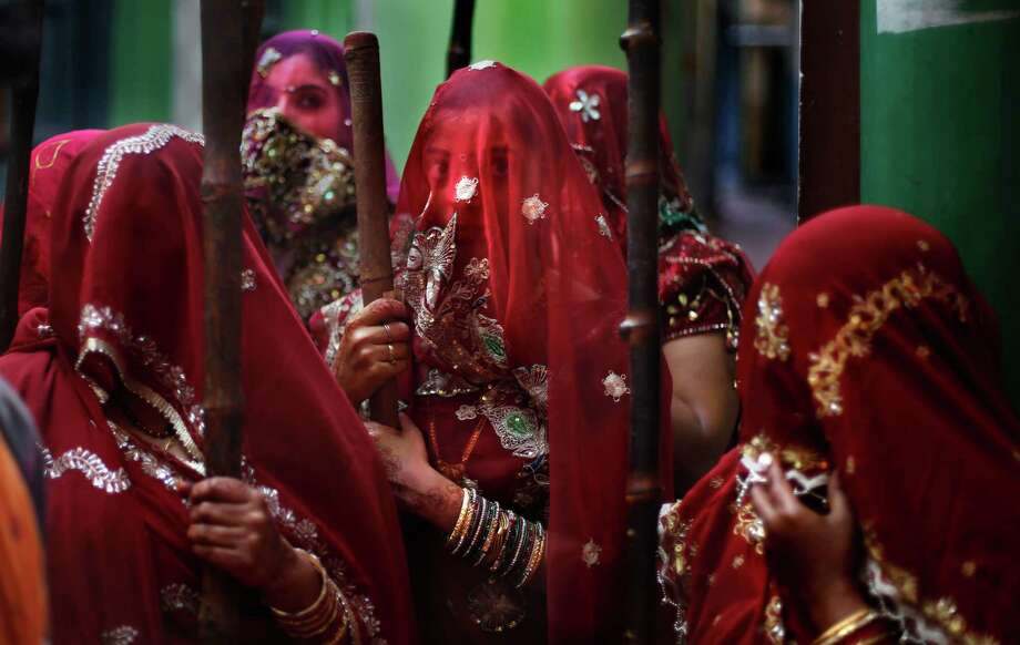 Indian women from Barsana village wait with a wooden sticks at the door step of their house for the arrival of villagers from Nandgaon, during the Lathmar Holy festival the legendary hometown of Radha, consort of Hindu God Krishna, in Barsana, 115 kilometers (71 miles) from New Delhi, India,Sunday, March 9, 2014. During Lathmar Holi the women of Barsana beat the men from Nandgaon, the hometown of Krishna, with wooden sticks in response to their teasing as they depart the town. Photo: Altaf Qadri, AP / AP