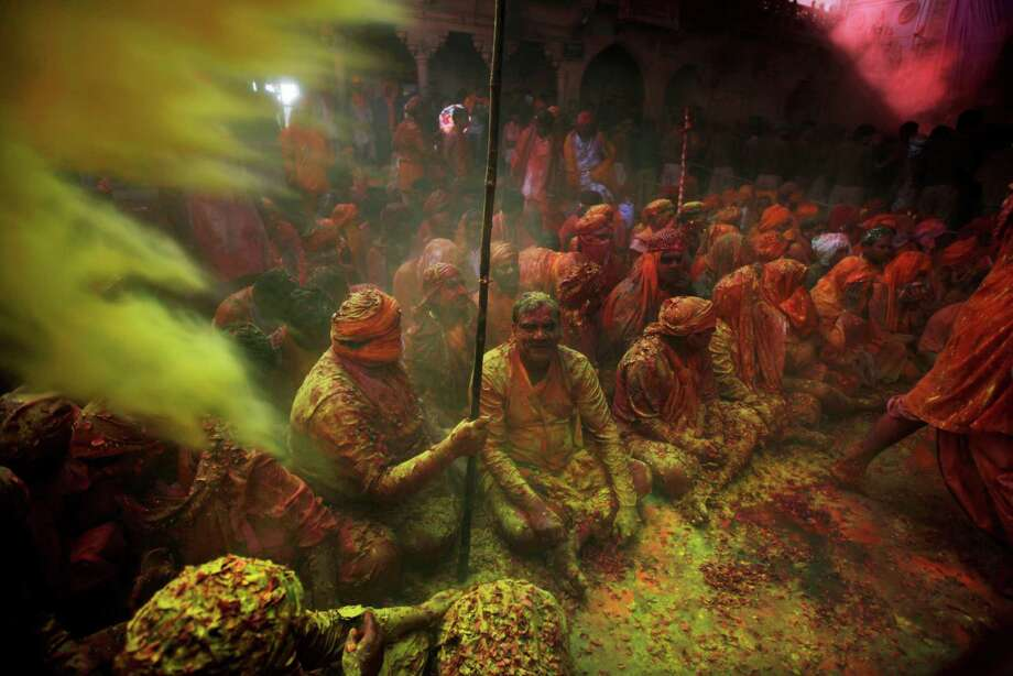 Hindu men from the village of Nangaon covered with colored powder sit on the floor during prayers at the Ladali or Radha temple before the procession for the Lathmar Holy festival, the legendary hometown of Radha, consort of Hindu God Krishna, in Barsana 115 kilometers ( 71 miles) from New Delhi, India, Sunday, March 9, 2014. During Lathmar Holi the women of Barsana beat the men from Nandgaon, the hometown of Krishna, with wooden sticks in response to their teasing as they depart the town. Photo: Altaf Qadri, AP / AP