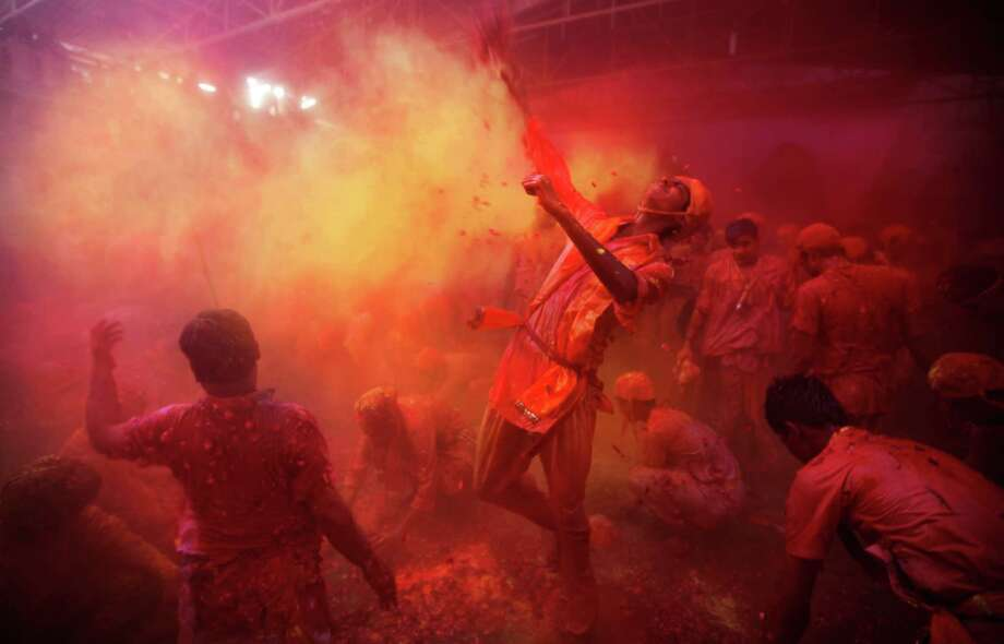 Hindu men from the village of Nangaon throw colored powder on others as they play holi at the Ladali or Radha temple before the procession for the Lathmar Holi festival, the legendary hometown of Radha, consort of Hindu God Krishna, in Barsana 115 kilometers ( 71 miles) from New Delhi, India, Sunday, March 9, 2014. During Lathmar Holi the women of Barsana beat the men from Nandgaon, the hometown of Krishna, with wooden sticks in response to their teasing as they depart the town. Photo: Altaf Qadri, AP / AP