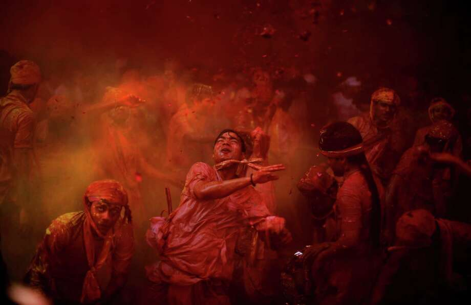 Hindu men from the village of Nangaon throw colored powder at each other as they play holi at the Ladali or Radha temple before the procession for the Lathmar Holi festival, the legendary hometown of Radha, consort of Hindu God Krishna, in Barsana 115 kilometers ( 71 miles) from New Delhi, India , in New Delhi, India, Sunday, March 9, 2014. During Lathmar Holi the women of Barsana beat the men from Nandgaon, the hometown of Krishna, with wooden sticks in response to their teasing as they depart the town. Photo: Altaf Qadri, AP / AP