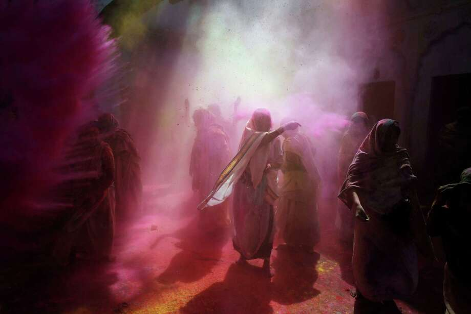 Indian Hindu widows play with colored powder as a part of Holi celebrations at the Pagal Baba Ashram in Vrindavan, India, Saturday, March 15, 2014. The widows, many of whom at times have lived desperate lives in the streets of the temple town, celebrated the festival at the ashram. After their husband's deaths the women have been banished by their families to the town where devotees believe Lord Krishna was born, for supposedly bringing bad luck. Photo: Rajesh Kumar Singh, AP / AP
