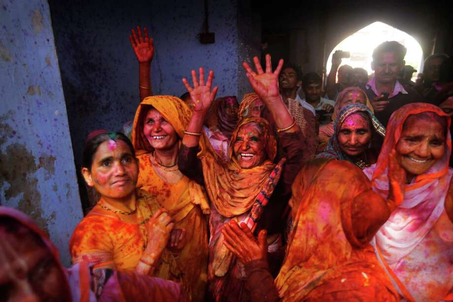 Indian Hindu widows play with colored water for the first time as part of Holi celebrations organized by a non-governmental organization Sulabh at the Meera Sahbhagini Ashram in Vrindavan, India, Friday, March 14, 2014. The widows, many of whom at times have lived desperate lives in the streets of the temple town, celebrated the festival at the century old ashram. After their husband's deaths the women have been banished by their families, for supposedly bringing bad luck, to the town where devotees believe Lord Krishna was born. Photo: Manish Swarup, AP / AP
