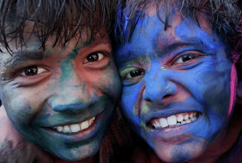 Indian children react to camera as they play with colored powder ahead of the Holi festival in Ahmadabad, India, Saturday, March 15, 2014. Holi, the Hindu festival of colors that also marks the advent of spring, is being celebrated across the country Monday. Photo: Ajit Solanki, AP / AP