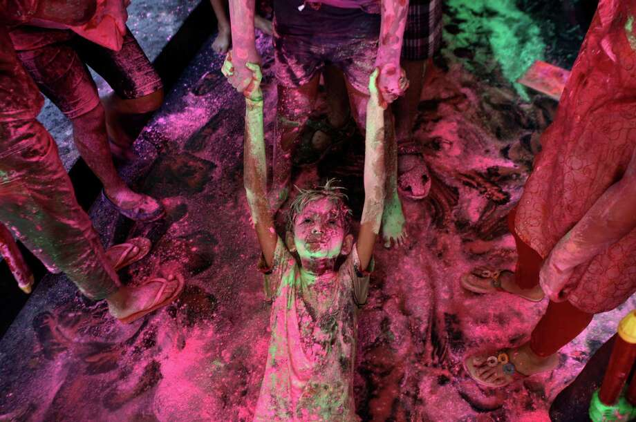 An Indian boy drags another on the floor of an apartment as they play with colors during the Holi festival in Chennai, India, Sunday, March 16, 2014. The festival also marks the advent of spring. Photo: Arun Sankar K, AP / AP
