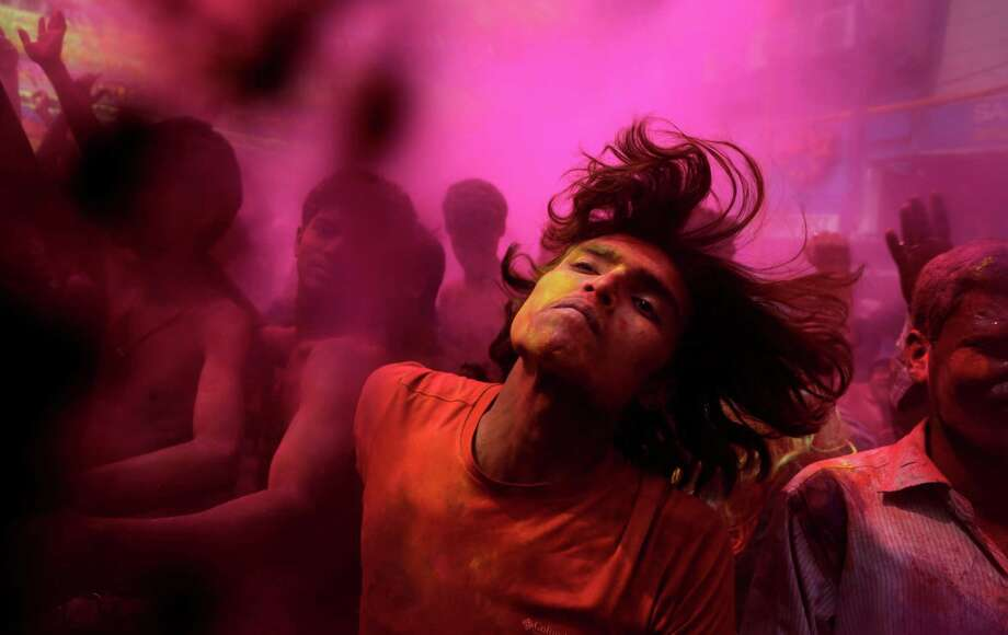 Indians, faces smeared with colored powder, dance during celebrations marking Holi, the Hindu festival of colors, in Gauhati, India, Monday, March 17, 2014. The festival also marks the advent of spring. Photo: Anupam Nath, AP / AP