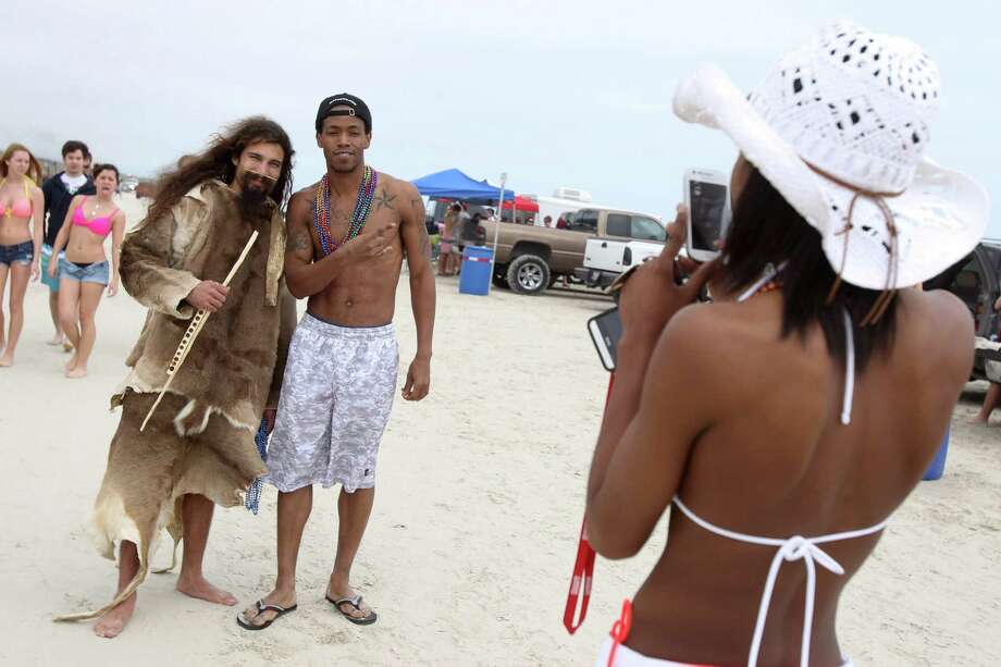 Denzell Boone of Longview, center, gets his picture taken with Nathan Martinez, Tuesday, March 11, 2014, as Martinez roams the beach wearing four deer skins during spring break on the beach in Port Aransas, Texas. Sun and warmer weather brought out bigger crowds at beaches across the Coastal Bend. Photo: Michael Zamora, AP / Corpus Christi Caller-Times
