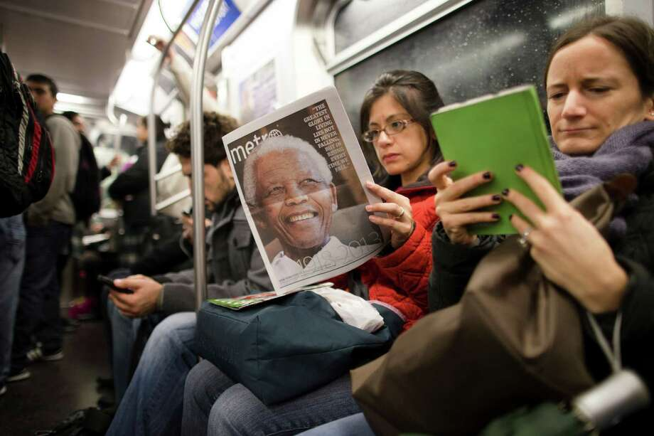 FILE - In this Dec. 6, 2013, file photo, a subway rider in New York reads a newspaper featuring news of the death of South African leader Nelson Mandela. Americans of all ages still pay heed to serious news even as they seek out the lighter stuff, choosing their own way across a media landscape that no longer relies on front pages and evening newscasts to dictate what's worth knowing, according to a new study from the Media Insight Project. (AP Photo/John Minchillo, File) ORG XMIT: WX108 Photo: John Minchillo / FR170537 AP