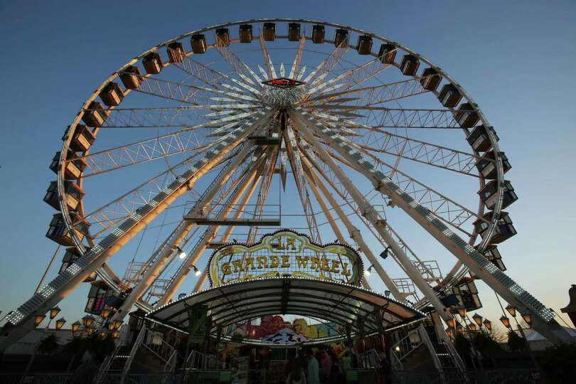People enjoy the Grande Wheel as the sun sets at the Carnival at the Houston Livestock Show and Ro