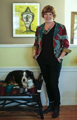 Fashion designer and DEMA boutique owner Dema Grim is seen at home with one her dogs, Georgie, on Tuesday, Feb. 25, 2014 in San Francisco, Calif.  Behind Grim is a lithograph by Bernard Buffet which is a favorite of her's.
