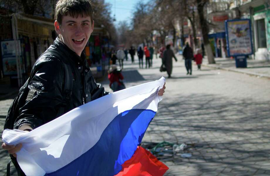 A local teenager waves with Russian flag in a street in Simferopol, Ukraine, on Monday, March 17, 2014. Ukraine's Crimean peninsula declared itself independent Monday after its residents voted overwhelmingly to secede and join Russia, while the United States and the European Union slapped sanctions against some of those who promoted the divisive referendum. (AP Photo/Ivan Sekretarev)  ORG XMIT: XIAS102 Photo: Ivan Sekretarev / AP