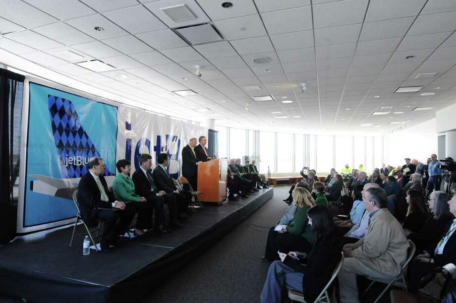 Senator Charles Schumer, at podium left, and Robin Hayes, president of JetBlue airlines, address those gathered during an event on Monday, March 17, 2014, in Colonie, N.Y., to announce that the airline will begin servicing the  Albany International Airport.   (Paul Buckowski / Times Union) Photo: Paul Buckowski / 00026177A