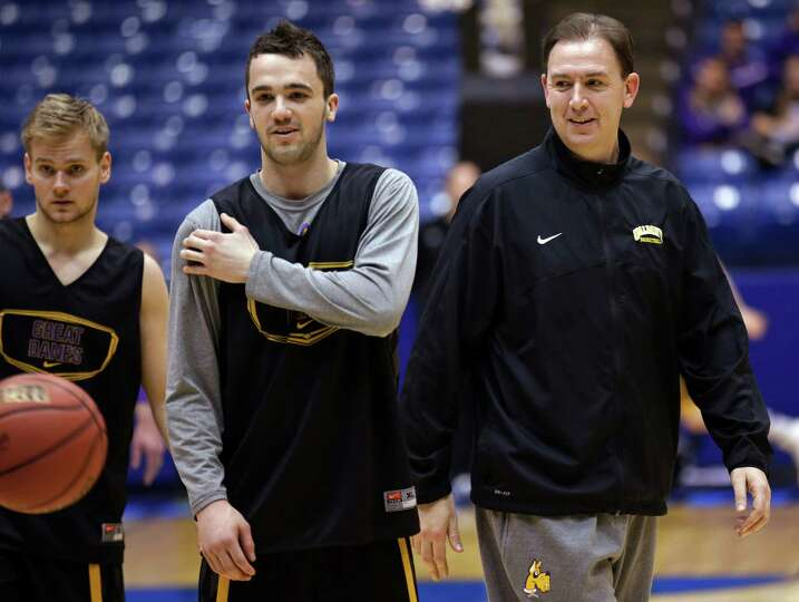 Albany head coach Will Brown, right, talks with guard Peter Hooley during practice for an NCAA colle