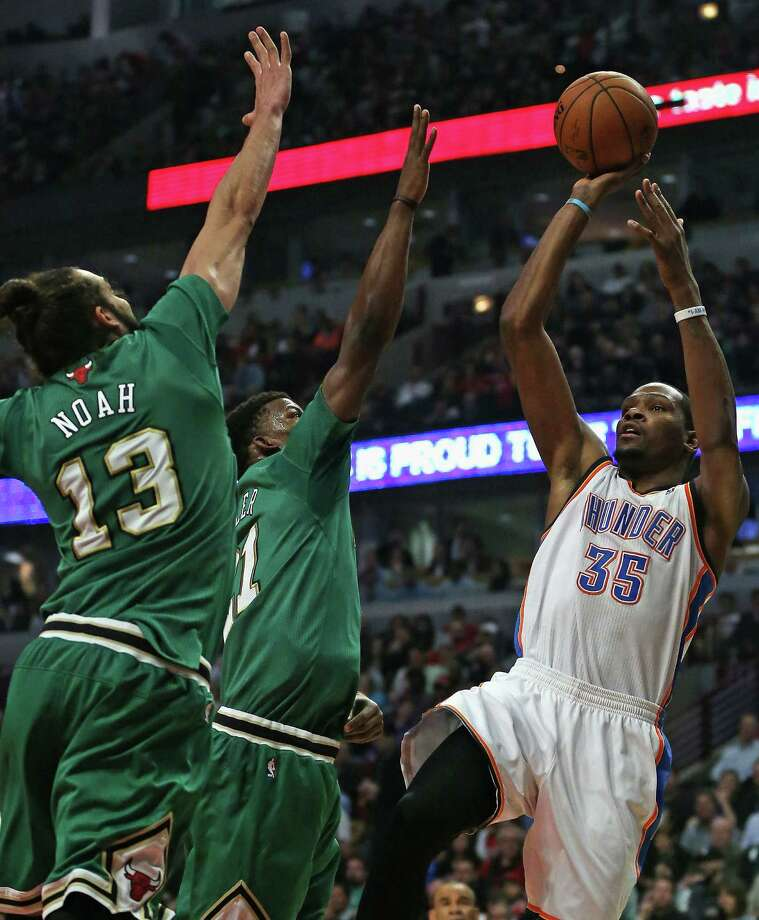 Kevin Durant shoots over Chicago's St. Patrick's Day uniform-clad Joakim Noah and Jimmy Butler during the Thunder's 97-85 victory at the United Center. Photo: Jonathan Daniel / Getty Images / 2014 Getty Images
