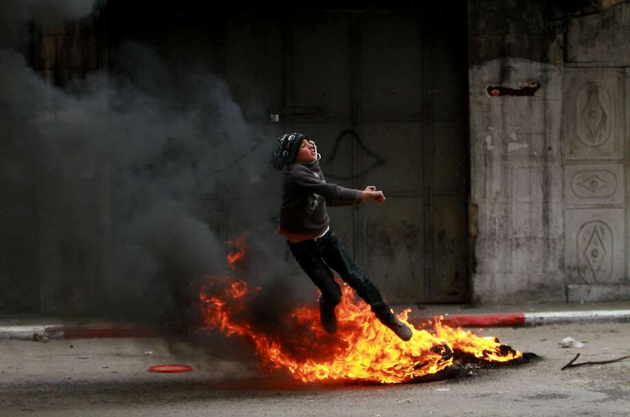 A Palestinian youth jumps over fire during clashes with Israeli soldiers after a support rally for Palestinian President Mahmoud Abbas in the West Bank city of Hebron, Monday, March 17, 2014. President Abbas met with the US President Barack Obama in Washington on Monday. (AP Photo/Nasser Shiyoukhi) Photo: Nasser Shiyoukhi, Associated Press
