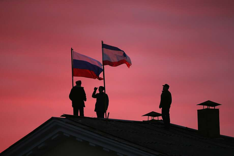BAKHCHYSARAI, UKRAINE - MARCH 17:  Cossack men install a Russian flag and a Crimean flag on the roof of the City Hall building on March 17, 2014 in Bakhchysarai, Ukraine. People in Crimea overwhelmingly voted to secede from Ukraine during a referendum vote on March 16 and the Crimean Parliament has declared Independence and formally asked Russia to annex them.  (Photo by Dan Kitwood/Getty Images) Photo: Dan Kitwood, Getty Images