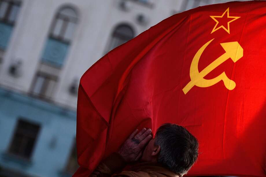 TOPSHOTS A man kisses the Soviet Union flag in Simferopol's Lenin Square on March 16, 2014. Polls opened today in a referendum on the peninsula of Crimea, in which voters are to voice their wish to either join Russia or become an effectively independent state connected to Ukraine.  AFP PHOTO / FILIPPO MONTEFORTEFILIPPO MONTEFORTE/AFP/Getty Images Photo: Filippo Monteforte, AFP/Getty Images
