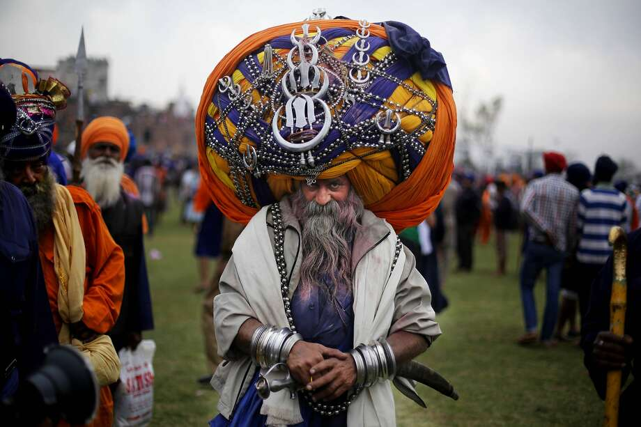 A Sikh warrior, wearing a huge turban attends the annual fair of 'Hola Mohalla' in Anandpur Sahib, in the northern Indian state of Punjab, Monday, March 17, 2014. Believers from various parts of northern India collect at the religious fair to celebrate the festival of Holi in a tradition set by the tenth Sikh guru Guru Gobind Singh in the seventeenth century. Nihangs, or Sikh warriors, display their martial skills and attire during the fair, believed to be maintained in the exact tradition as set by the Guru. (AP Photo/Altaf Qadri) Photo: Altaf Qadri, Associated Press