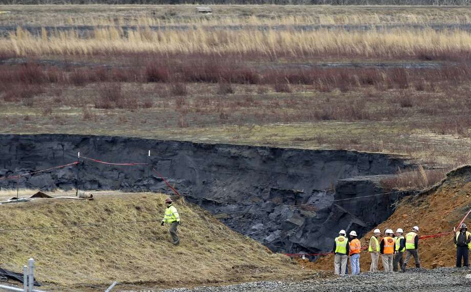 FILE - In a Wednesday, Feb. 5, 2014 file photo, Duke Energy engineers and contractors survey the site of a coal ash spill at the Dan River Power Plant in Eden, N.C. as state and federal environmental officials continued their investigations of the spill into the river. A federal grand jury is convening Tuesday, March 18, 2014, as part of a widening criminal investigation triggered by the massive Duke Energy coal ash spill that coated 70 miles of the Dan River with toxic sludge. (AP Photo/Gerry Broome, File) Photo: AP