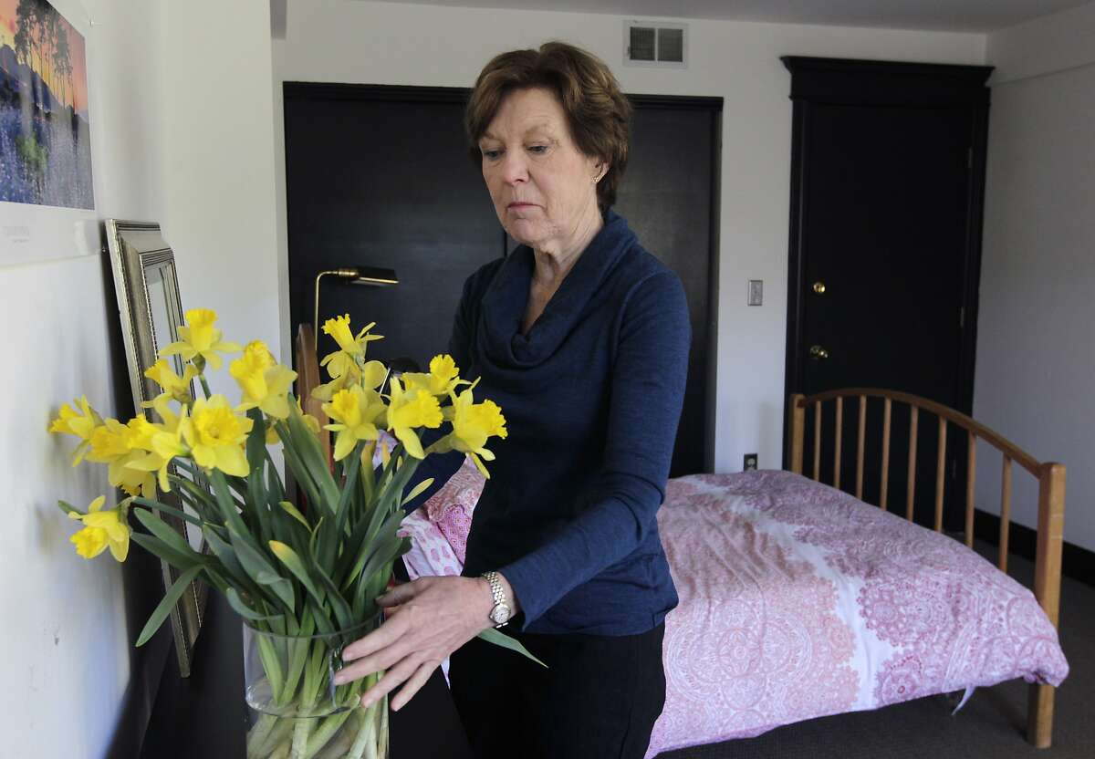 Lorraine Rorke Bader arranges fresh flowers in a room at her home before an overnight guest arrives in San Francisco, Calif. on Saturday, Jan. 25, 2014. Bader rents out the room, with a 3-night minimum stay, for $120 a day using the Airbnb service.