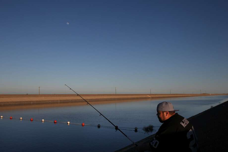 Matthew Moreno, 29, fishes with his friends at the end of the day at the San Luis Canal, California Aqueduct March 13, 2014 outside of Los Banos, Calif. Water shortages in the Central Valley are a big concern for residents and farmers, alike. Aaron Mandell, Co-founder and Chairman of WaterFX, is hoping to build a thermal, solar run desalination plant in neighboring Firebaugh, so they can tap into the sub surface ground water that is too high minerals such as salt, selenium and boron to be used for agriculture or personal use. Photo: Leah Millis, The Chronicle