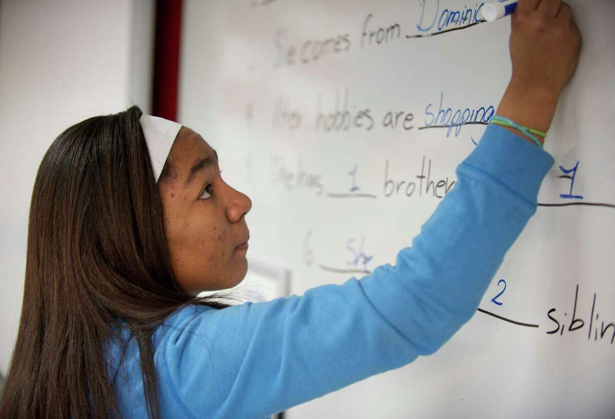 Danbury High School student Mairely Rubio, age 18, fills out a form on the white board during an acculturation class at the Danbury, Conn, school, on Tuesday, March 18, 2014. The class is for newcomers from other countries with limited english proficiency. Rubio came to the United States from the Dominican Republic and is an advanced English language learner who helps out in the class.