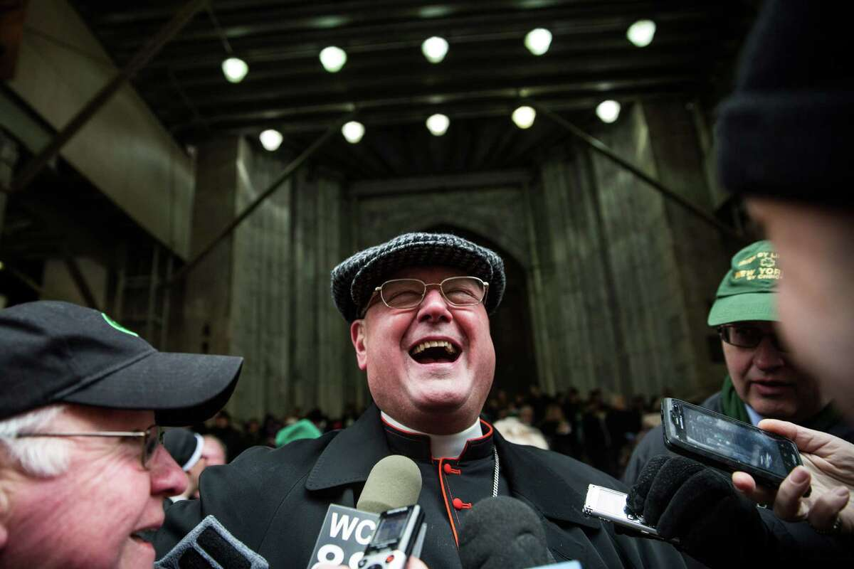 NEW YORK, NY - MARCH 17: Archbishop of New York, Cardinal Timothy Dolan of the Roman Catholic Church laughs while talking to reporters while watching the annual St. Patrick's Day Parade along Fifth Ave in Manhattan on March 17, 2014 in New York City. Political controversy surrounded this year's parade, as New York City Mayor Bill De Blasio decided not to march due to the parade organizer's policy to ban participants that identify themselves as lesbian, gay, bisexual or transgender. Heineken and Guinness announced earlier that they would drop their sponsorship of the parade for along the same reasons. (Photo by Andrew Burton/Getty Images) *** BESTPIX *** ORG XMIT: 479153251