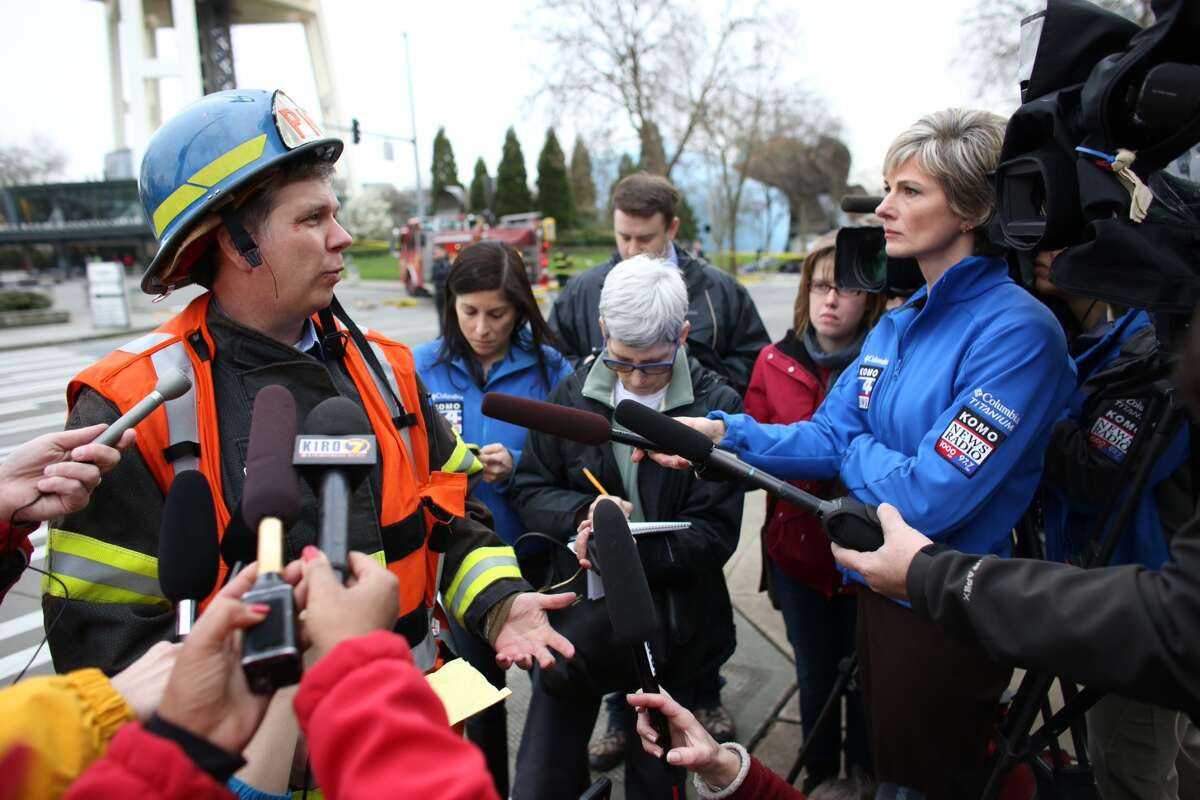 Kyle Moore of the Seattle Fire Department briefs reporters.