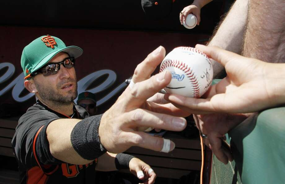 San Francisco Giants' Marco Scutaro signs autographs prior to a spring training baseball game against the Los Angeles Angels, Monday, March 17, 2014, in Tempe, Ariz. Photo: Ross D. Franklin, Associated Press