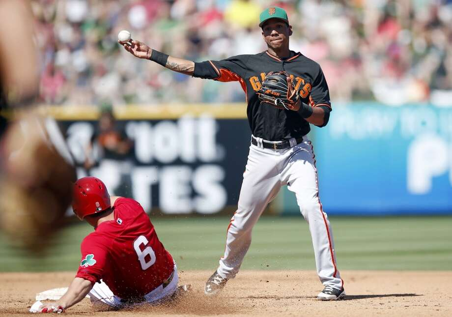 San Francisco Giants' Ehire Adrianza, right, forces out Los Angeles Angels' David Freese (6) at second base in the fourth inning of a spring training baseball game, Monday, March 17, 2014, in Tempe, Ariz. Photo: Ross D. Franklin, Associated Press