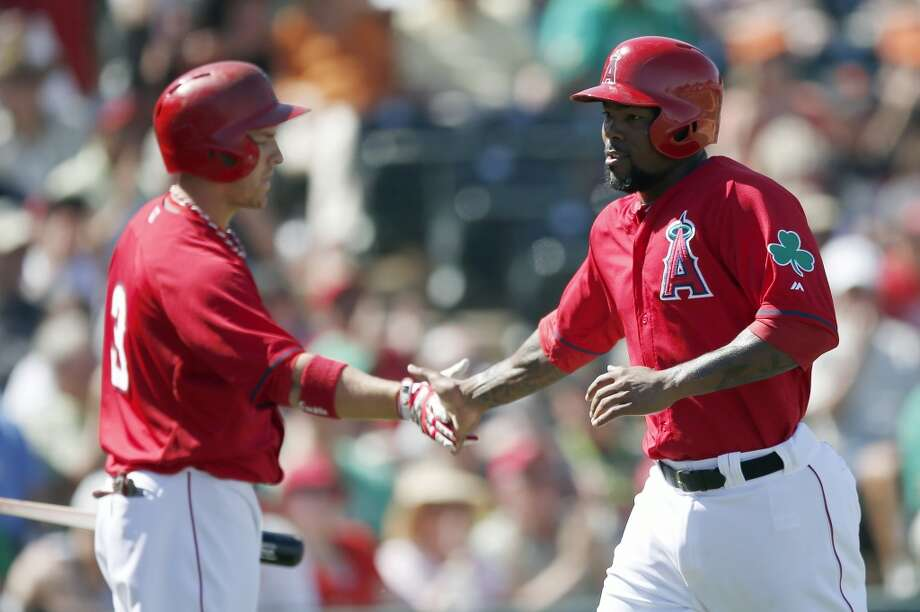 Los Angeles Angels' Howie Kendrick, right, shakes hands with teammate J.B. Shuck (3) after Kendrick scores a run against the San Francisco Giants in the fourth inning of a spring training baseball game, Monday, March 17, 2014, in Tempe, Ariz. Photo: Ross D. Franklin, Associated Press