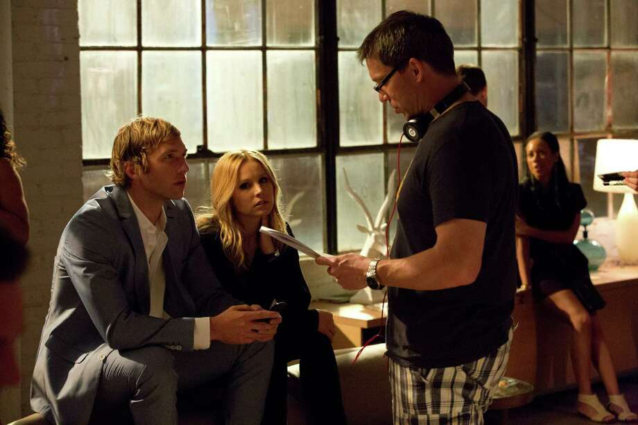 "This image released by Warner Bros. Pictures shows, from left, actors Ryan Hansen and Kristen Bell with director Rob Thomas on the set of ""Veronica Mars."" Thomas realized he might make movie history by using Kickstarter to crowd-fund his ""Veronica Mars"" movie. He was less clear on what it meant to sign more than 5,000 movie posters as a promised reward for contributing backers. Of all the rewards offered to donors of ""Veronica Mars"" _ everything from a digital copy of the script for $10 to a walk-on cameo for $10,000 _ the most taxing pledge has been fulfilling the thousands of posters to be signed by Thomas and the cast. (AP Photo/Warner Bros. Pictures, Robert Voets) ORG XMIT: NYET314 Photo: Robert Voets / Warner Bros. Pictures"