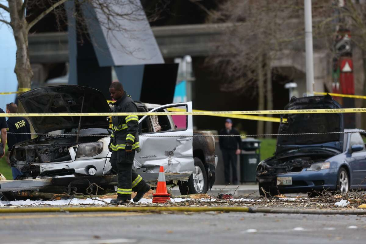 A Seattle firefighter walks by the wreckage. Three cars were set on fire and a 38-year-old man was critically injured.