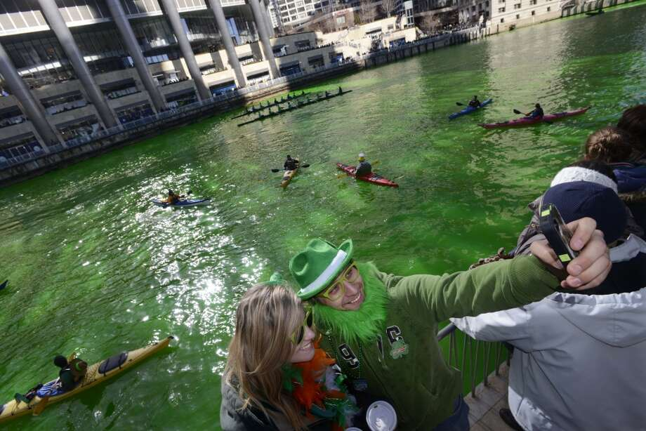 Elizabeth Saathoff left, and Scott Wrobel right, both of Chicago, photograph themselves with a smartphone after the Chicago River was dyed green ahead of the St. Patrick's Day parade in Chicago, Saturday, March 15, 2014. (AP Photo/ Paul Beaty) Photo: Associated Press