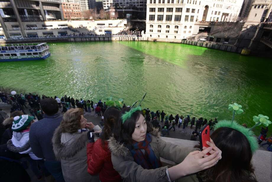 A reveler takes a photo of herself in front of the Chicago River dyed green ahead of the St. Patrick's Day parade in Chicago on Saturday, March 15, 2014. The annual dying has been done since 1962. (AP Photo/Paul Beaty) Photo: Associated Press