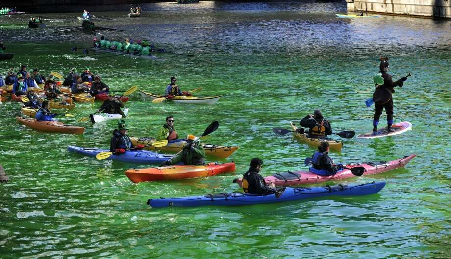 Kayakers float on the Chicago River after it was dyed green ahead of the St. Patrick's Day parade in Chicago, Saturday, March 15, 2014. (AP Photo/Paul Beaty) Photo: Associated Press
