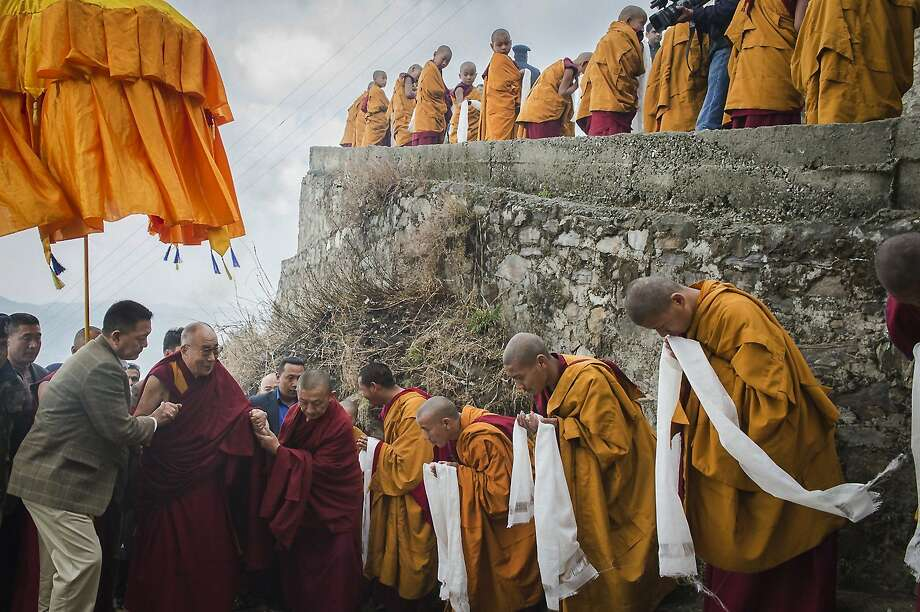 Tibetan Buddhist monks holding ceremonial scarfs stand in a line to welcome their spiritual leader the Dalai Lama, fourth left, as he arrives at the Jhonang Takten Phuntsok Choeling monastery in Shimla, India, Tuesday, March 18, 2014. (AP Photo/Tenzin Choejor) Photo: Tenzin Choejor, Associated Press