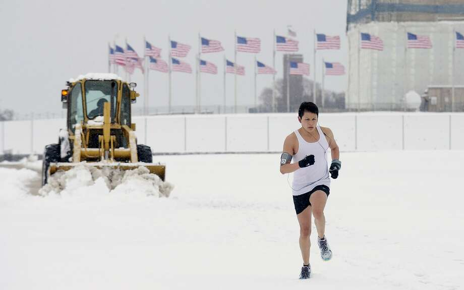 Winter just doesn't want to end in Washington, where a lightly dressed runner tries to stay ahead of the plow on the Washington Monument grounds. Photo: Susan Walsh, Associated Press