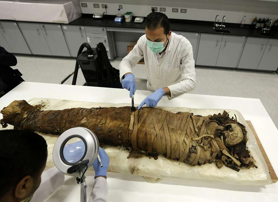 Wrap session: A conservator cleans a female mummy dated to Pharaonic late period (712-323 BC) in the conservation center of Egypt's Grand Museum. Egypt's antiquities minister says construction has begun on the main hall of a massive new museum by the Pyramids, the final phase of a complex that's expected to house 100,000 ancient artifacts. Photo: Amr Nabil, Associated Press