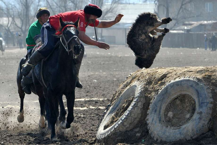 He shoots! He scores!A Kyrgyz rider puts the biscuit (a dead goat) in the basket (a well) during a Buzkashi match in Bishek. Buzkashi is also known as goat carcass polo. Photo: Vyacheslav Oseledko, AFP/Getty Images