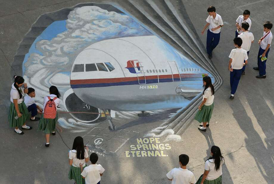 "Gone underground: A mural suggests that missing Malaysia Airlines Flight 370 might be hiding under the grounds of Benigno ""Ninoy"" Aquino High School in Makati Philippines. Photo: Ted Aljibe, AFP/Getty Images"