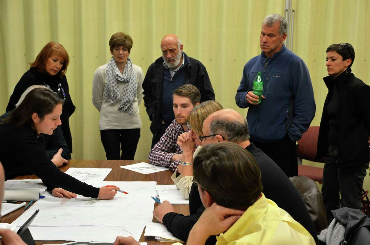 Members of the public look over the shoulders of Compo Beach Site Improvement Committee members as they review proposals for a new master plan last week.