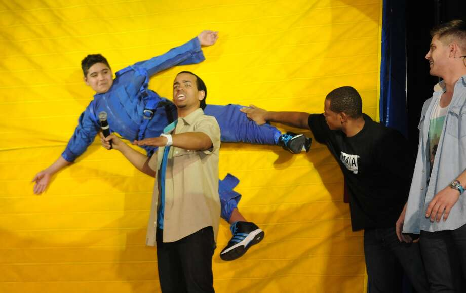 Kenneth Leal, 12, left, gets velcro-walled during a Newtonís Three Laws of Motion demonstration  presented by John James, center, of Atlanta and the Forces in Motion Live cast at Wunderlich Intermediate School in Klein. Photo: Jerry Baker, Freelance